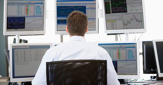 man looking at computer screens displaying data