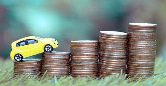 a toy car standing on stack of coins